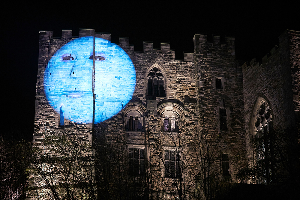 A projection of a moon with a face on Durham Castle's wall.
