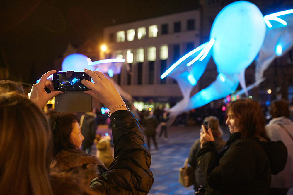 People photographing an installation floating in the sky in Durham's Market Square.