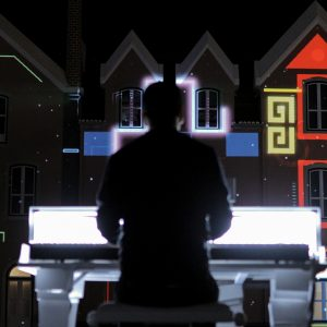 Man playing piano with multi-coloured projections in the background.
