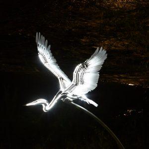 Sculpture of heron against dark night's sky.
