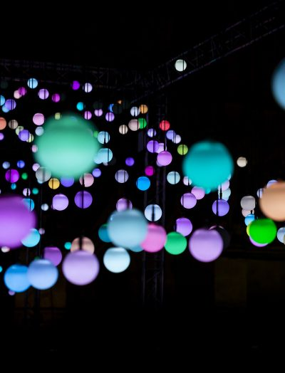 Colourful orbs against black background.