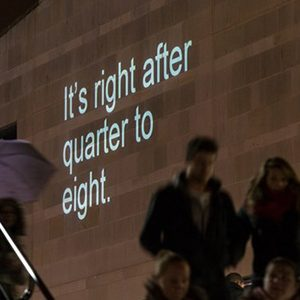 The words 'It's right after quarter to eight' projected on a wall.