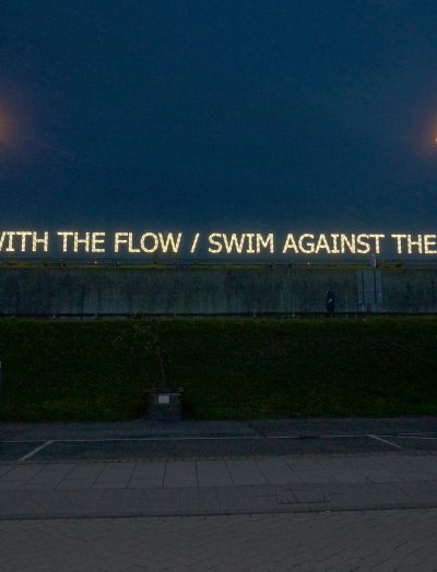 GO WITH THE FLOW / SWIM AGAINST THE TIDE neon sign above a carpark